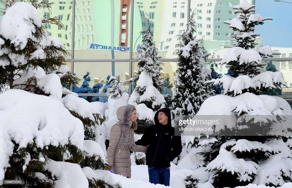 A couple laughs as they stand near the snow covered trees in the Belarus capital Minsk, on January 21, 2013. Snow fell today across Minsk as the temperatures dropped to -12 C (10 F).