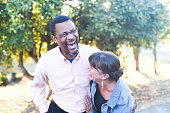 A middle aged couple in an interracial relationship laugh affectionately with each other.