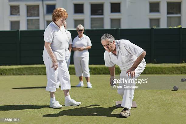 Couple lawn bowling on grass