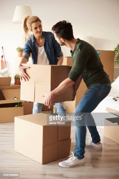 Couple laying cardboard boxes on the stack. Debica, Poland
