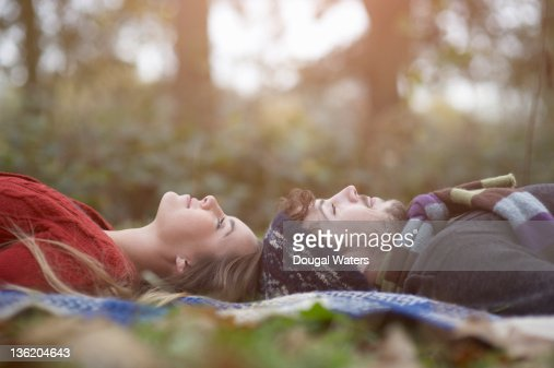 Couple laying head to head in countryside. : Stock Photo
