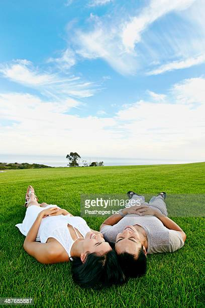 Couple laying in grass in rural landscape