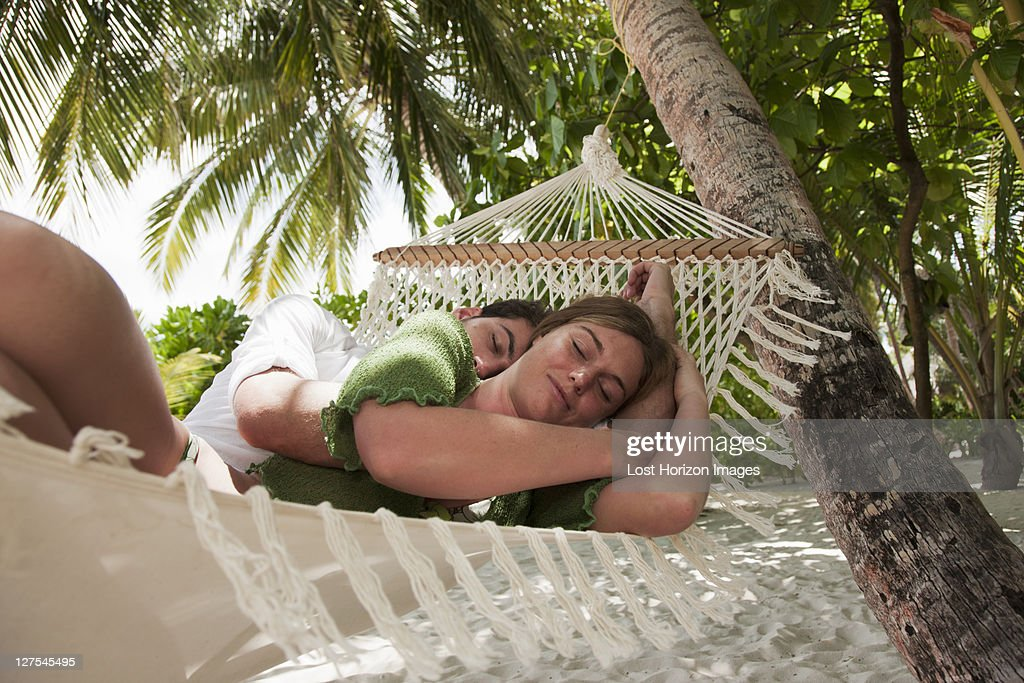 Couple laying in hammock on beach : Stock Photo