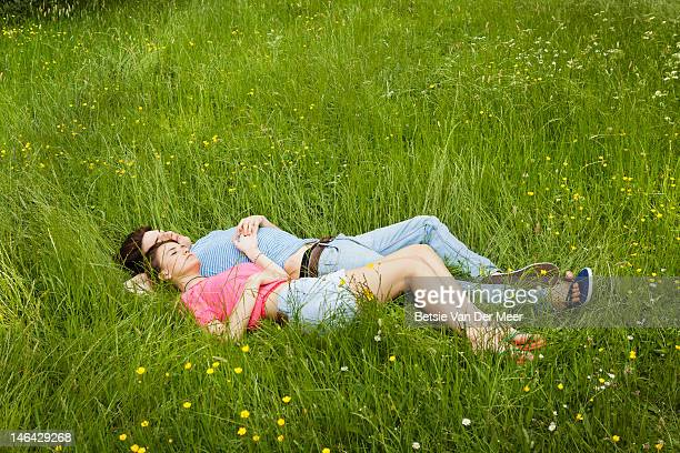 Couple laying in long grass with buttercups.