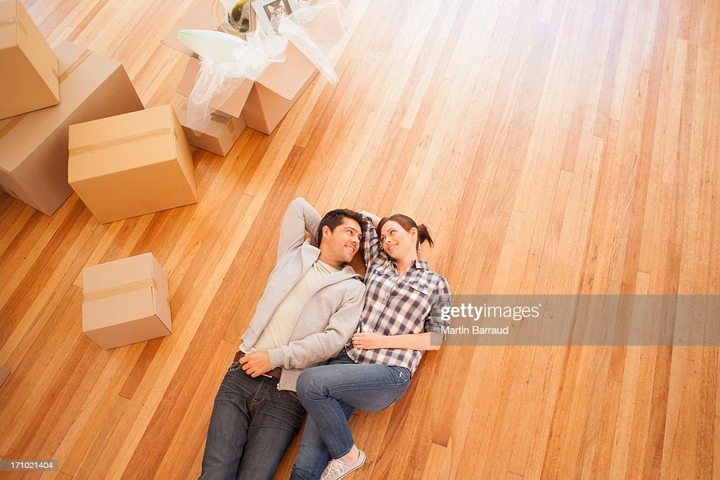 Couple laying on floor of new house : Stock Photo