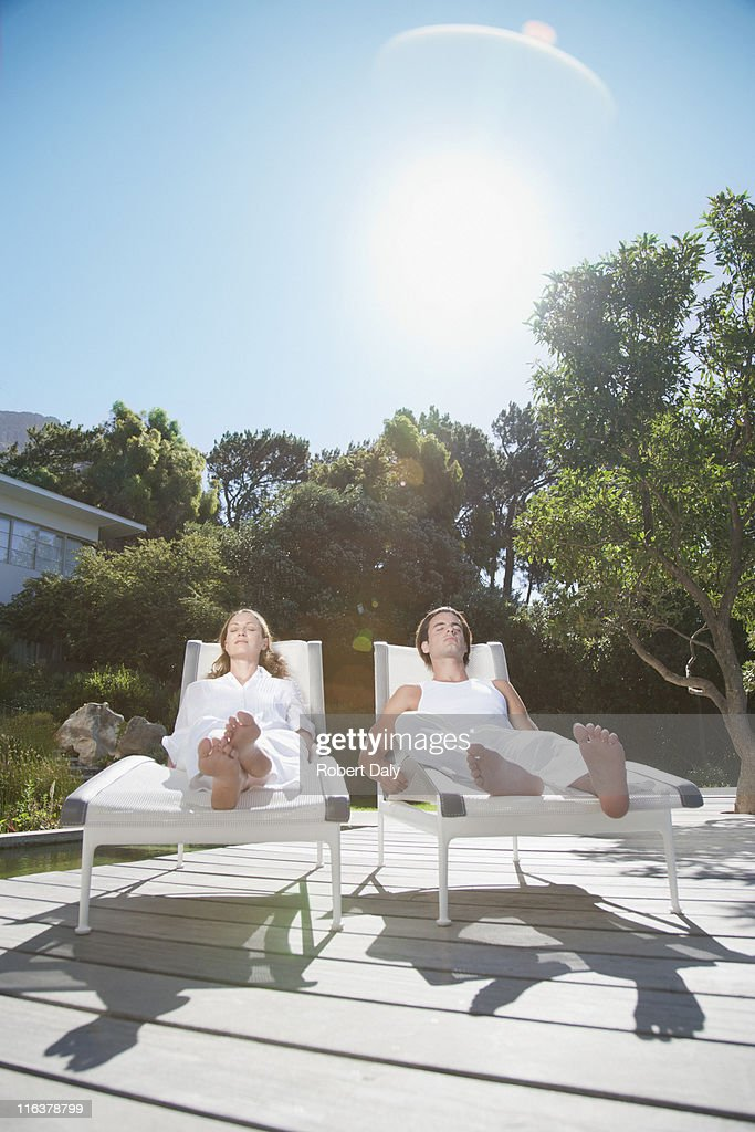Couple laying on lounge chairs on patio : Stock Photo