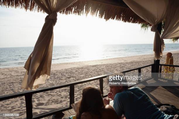 Couple laying on porch enjoying beach and ocean