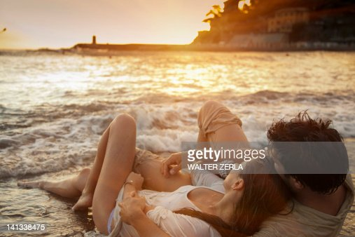 Couple laying on sand at beach : ストックフォト