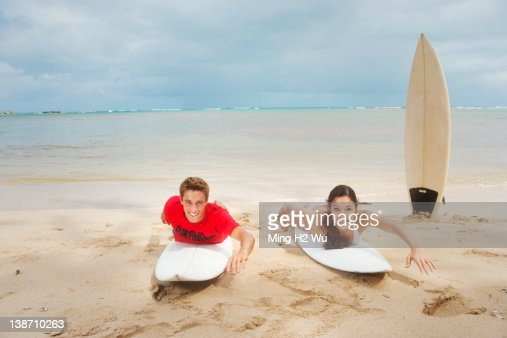 Couple Laying On Surfboards On Beach Stock Photo | Getty ...