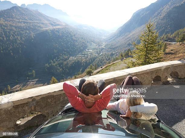Couple lean on car hood, look towards distant mtns