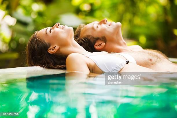 Casal leaned na borda de uma piscina tropical.