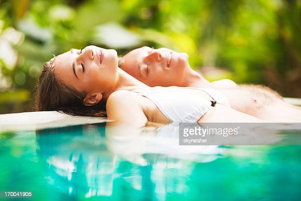 Couple leaned on the edge of a tropical pool.