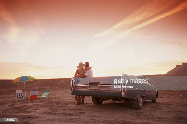 Couple leaning against car in desert, sunset,  rear view, picnic table