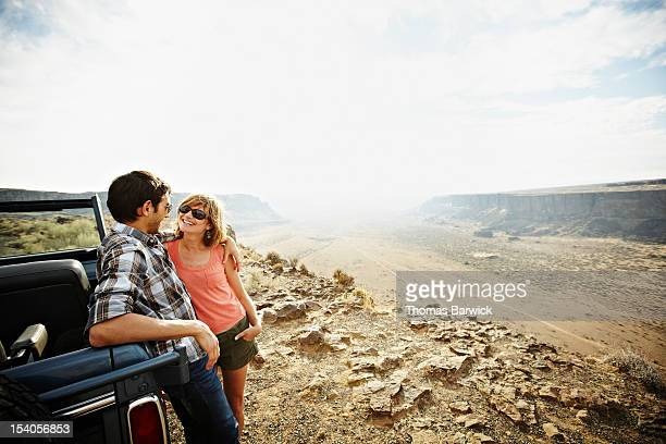 Couple leaning against convertible on side of road