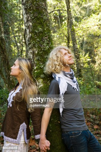 Couple leaning against tree holding hands , Humboldt , California , USA