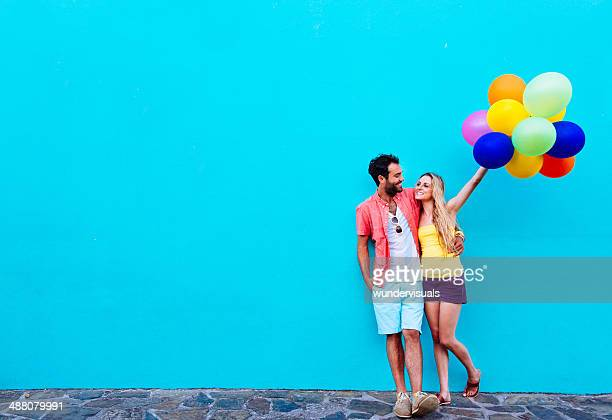 Couple leaning blue wall with balloons