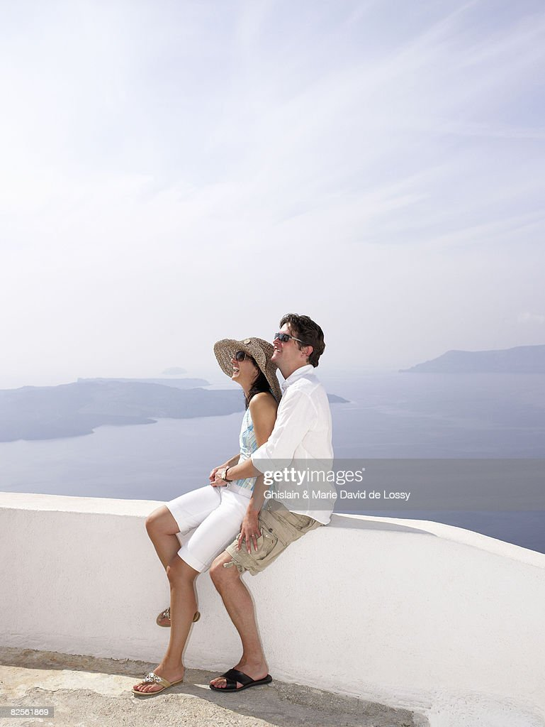 Couple leaning on a low wall, sea view