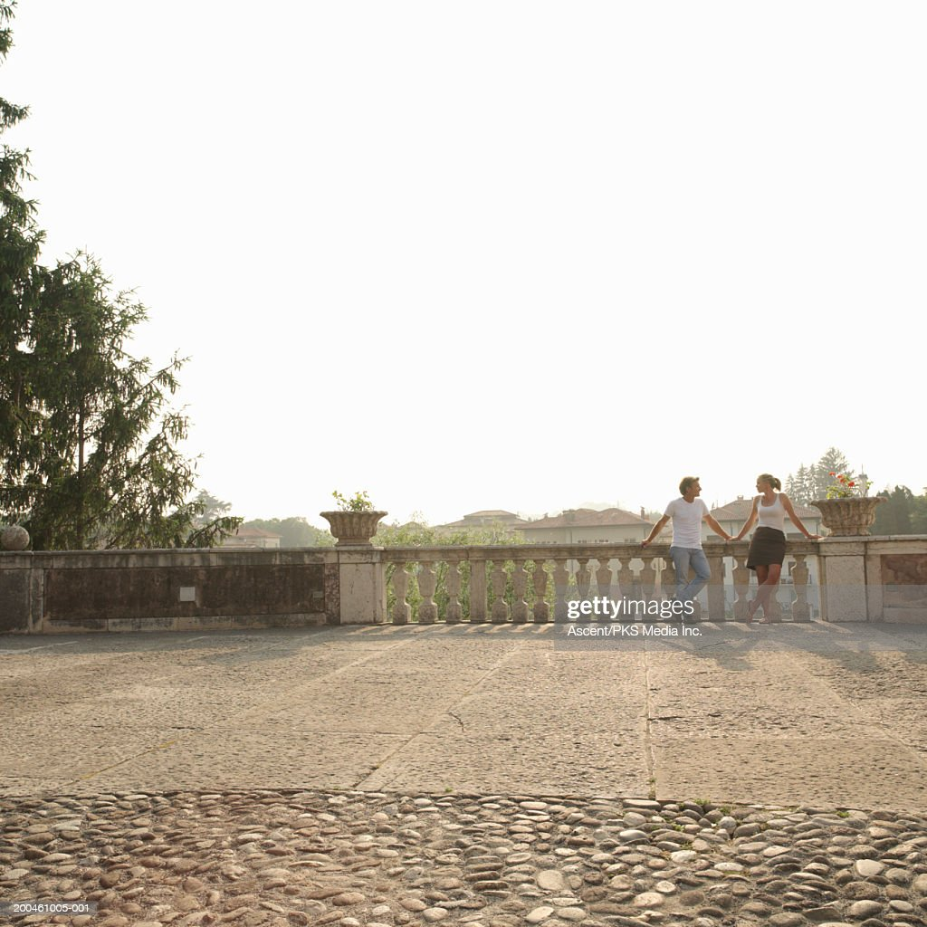 Couple leaning on balustrade at edge of plaza, sunset : ストックフォト