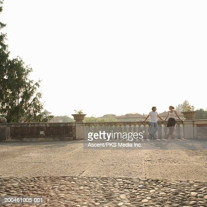 Couple leaning on balustrade at edge of plaza, sunset : Stock Photo