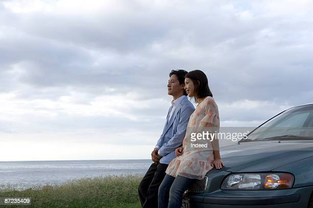 Couple leaning on car, looking at view