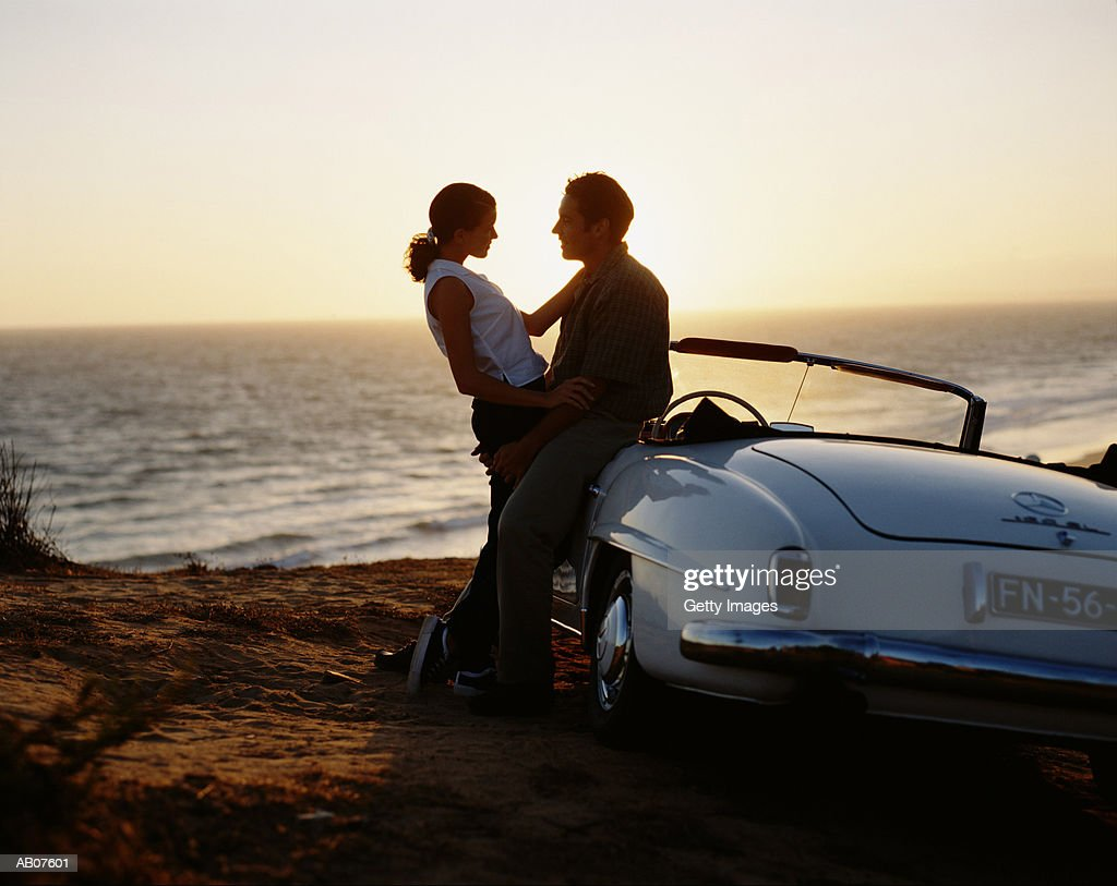 Couple leaning on  convertible on beach, sunset : Stock Photo