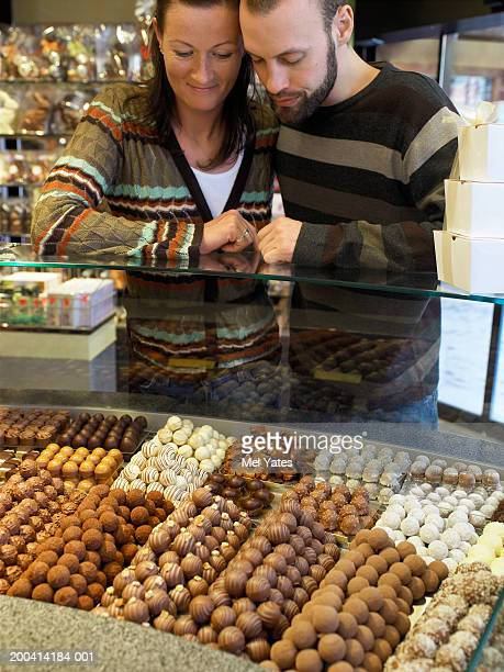 Couple leaning on counter in chocolate shop, view from behind counter