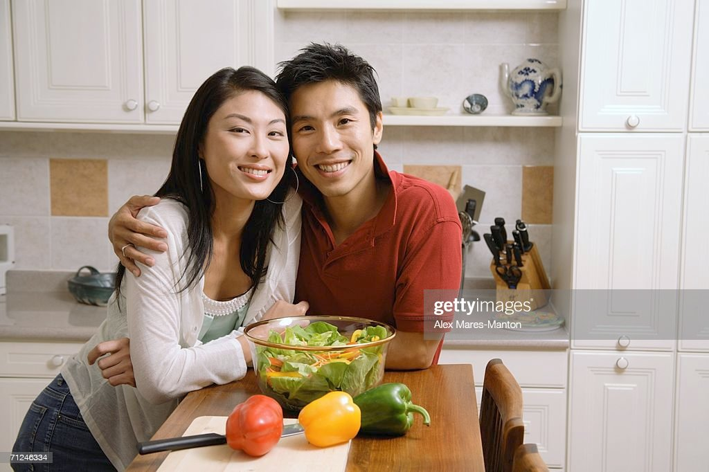 Couple leaning on kitchen counter, smiling at camera : Stock Photo
