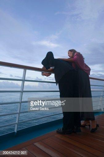 Couple leaning on rail of cruise ship, at dusk : Stock Photo