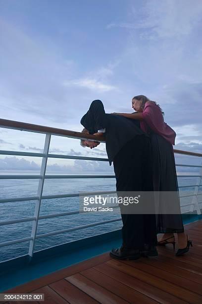 Couple leaning on rail of cruise ship, at dusk