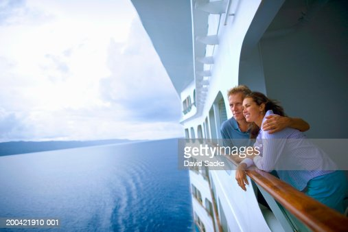Couple leaning on rail of cruise ship, looking at ocean