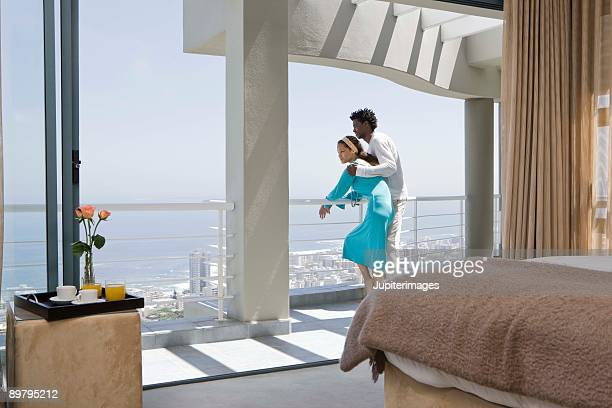 Couple leaning on railing of balcony of hotel room
