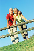 Couple leaning on split-rail fence