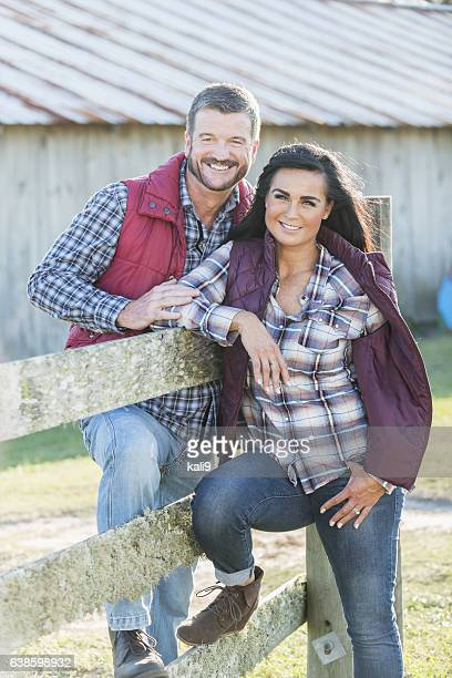 Couple leaning on wood fence outside barn