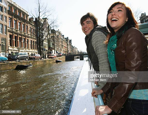 Couple leaning over edge of boat on canal, smiling