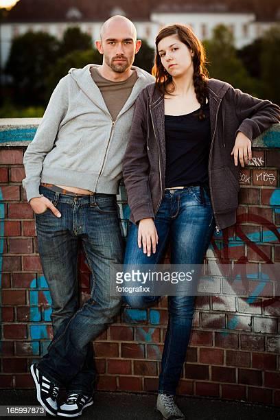 Paar lehnt sich gegen eine Wand mit cool attitude