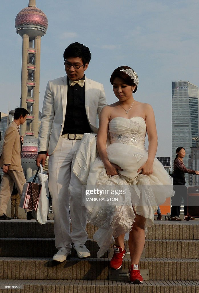 A couple leave the historic Bund after having wedding photos taken in Shanghai on October 29, 2013. Divorce rates in China's two wealthiest cities, Beijing and Shanghai, have soared after the announcement of a property tax that includes a loophole for couples who split up. Nearly 40,000 couples divorced in the Chinese capital in the first nine months of this year, jumping 41 percent on the same period in 2012, according to figures released by Beijing's civil affairs officials this month. AFP PHOTO/Mark RALSTON