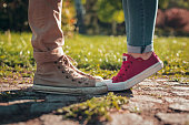Love couple legs in sneakers. Girl in red sneakers standing on a toes. Guy in ocher sneakers and denim.