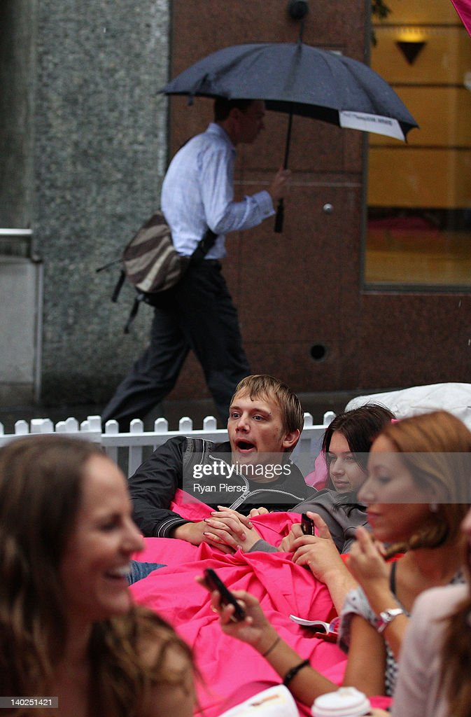 A couple lie in bed as morning commuters make their way to work during the The World's Biggest Breakfast in Bed Guinness World Record Attempt at Martin Place on March 2, 2012 in Sydney, Australia.