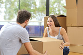 Happy couple or marriage lifting boxes moving home