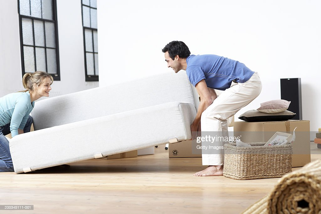 Couple lifting sofa, smiling, side view