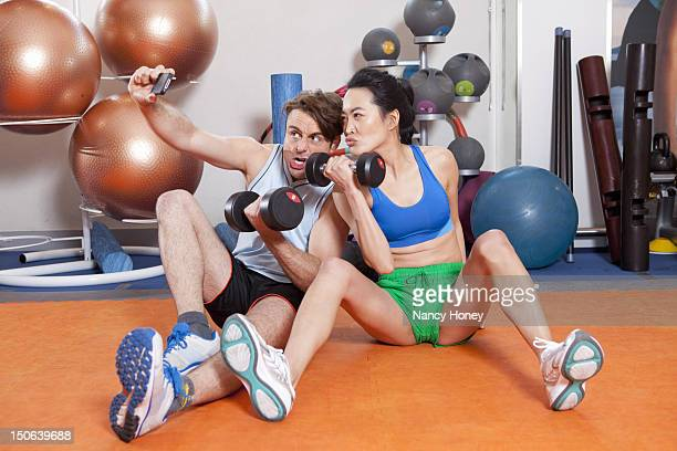Couple lifting weights in gym