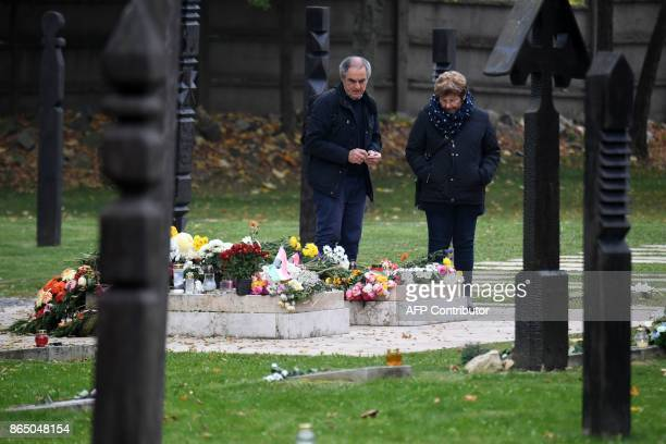 A couple lights candles at the grave at the Koztemeto cemetery for the victims of the 1956 uprising against Soviet occupation in Budapest on October...