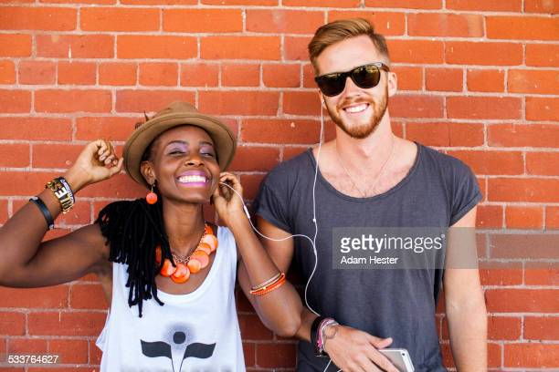 Couple listening to earbuds near brick wall