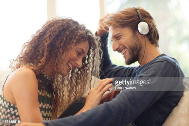 Couple listening to headphones on sofa