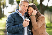 Couple Listening To MP3 Whilst Walking In Autumn Park