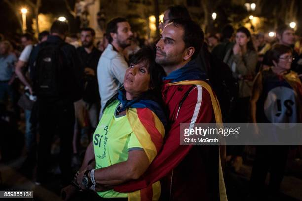 A couple listens on as they watch a big screen after Catalan President Carles Puigdemont suspended the declaration of independence outside the...