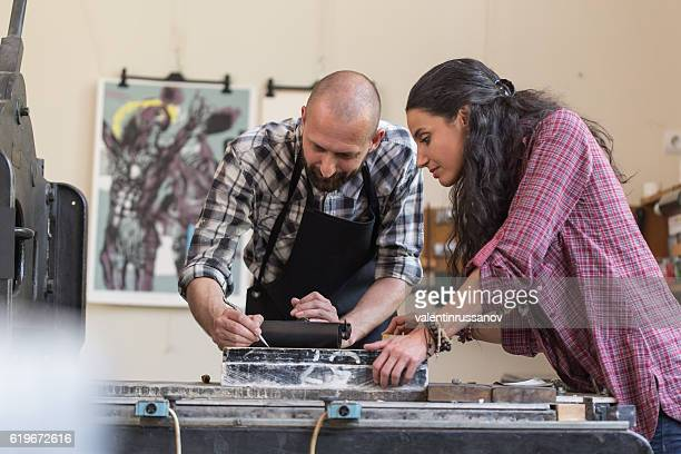 Couple lithographs using printing press at workshop