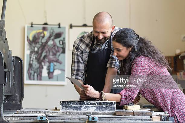 Couple lithography workers looking at new product at workshop