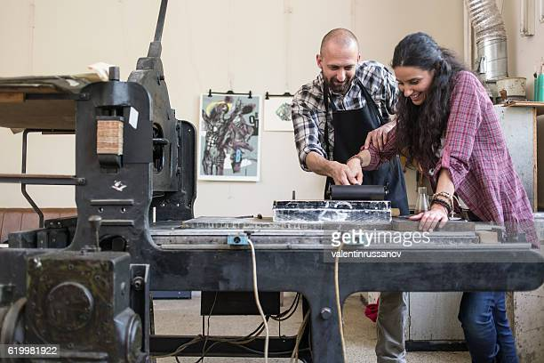 Couple lithography workers using printing press at workshop