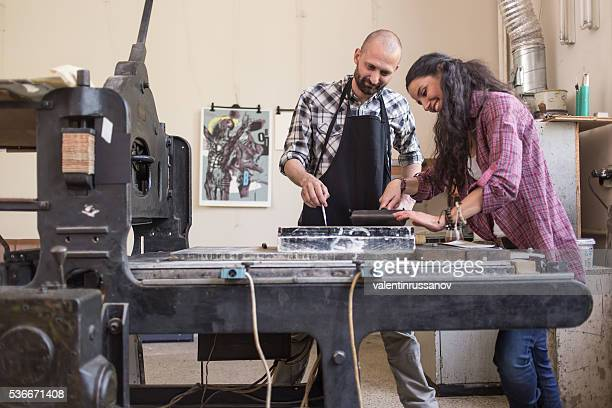 Couple lithography workers using printing press